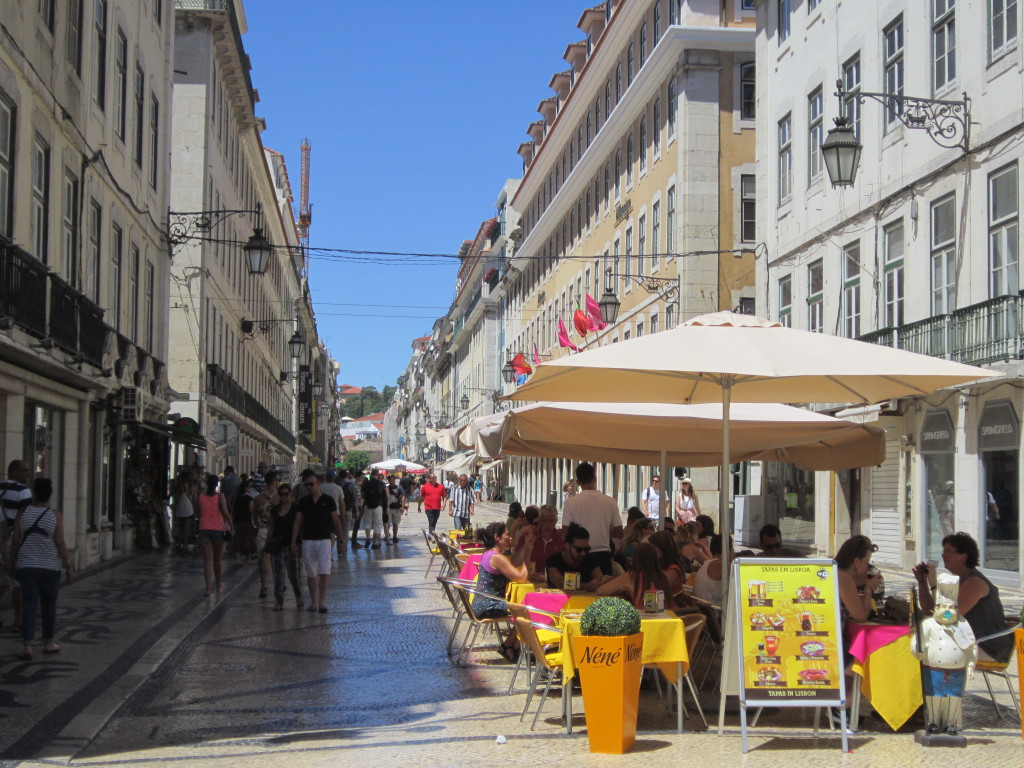 Rua Augusta leagă, pietonal, pe sub Arco Triunfal, Praça Rossio de Praça do Comércio (situată pe țărmul estuarului Tejo). Atenție la genți, la notele de plată și la cetățenii... români